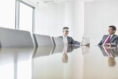 Homens de negócios de sorriso que falam na sala de conferências foto de stock royalty free