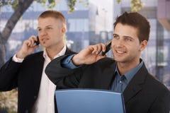 Homens de negócios de sorriso que fazem o atendimento de telefone Fotos de Stock