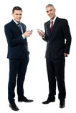 Homens de negócios de sorriso que usam o telefone celular foto de stock