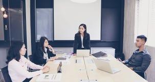 Homens de negócios e grupo asiáticos que usa o caderno para encontrar a sério imagens de stock