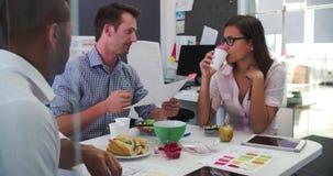 Homens de negócios e mulher de negócios Having Working Lunch no escritório vídeos de arquivo