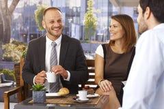 Homens de negócios e mulher de negócios que relaxam no café Fotografia de Stock