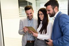 Homens de negócios e mulher de negócios que usa a tabuleta no escritório Fotos de Stock