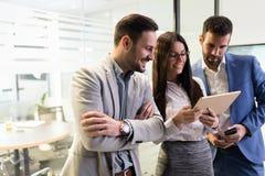 Homens de negócios e mulher de negócios que usa a tabuleta no escritório Imagem de Stock