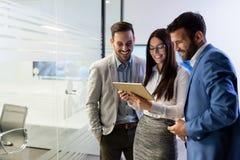 Homens de negócios e mulher de negócios que usa a tabuleta no escritório Foto de Stock Royalty Free
