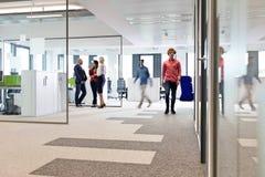 Homens de negócios e mulheres de negócios no corredor do escritório Imagens de Stock