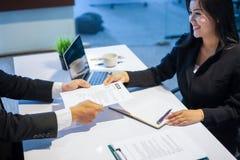 Homens de negócios e mulheres de negócios que discutem originais para o trabalho inter imagem de stock