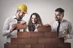 Homens de negócios e uma mulher de negócio que constrói uma parede Fotos de Stock Royalty Free