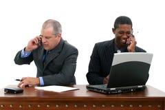 Homens de negócios em telemóveis na mesa Imagem de Stock