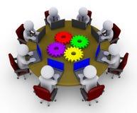 Homens de negócios em torno da tabela com portáteis e rodas denteadas Fotografia de Stock Royalty Free