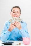 homens de negócios em uma camisa azul que conta dólares acumulados Fotos de Stock