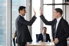 Homens de negócios executivos entusiasmados felizes dos colegas que dão altamente cinco no escritório imagem de stock