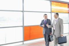 Homens de negócios felizes que falam ao andar na estação de estrada de ferro foto de stock royalty free
