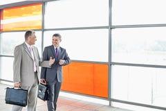 Homens de negócios felizes que falam ao andar na estação de estrada de ferro imagem de stock royalty free