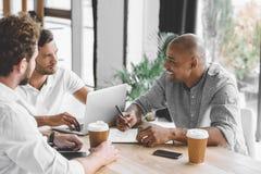 homens de negócios multiculturais que trabalham no portátil e que discutem a estratégia empresarial imagens de stock