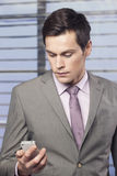 Homens de negócios no escritório que olham o telefone celular Imagens de Stock