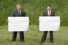 Homens de negócios no fundo da grama verde imagens de stock
