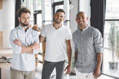 homens de negócios novos multi-étnicos que olham a câmera ao estar imagem de stock royalty free
