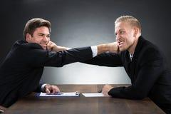 Homens de negócios novos que lutam na mesa de madeira imagem de stock