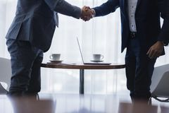 Homens de negócios que agitam as mãos após a reunião bem sucedida fotos de stock
