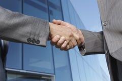 Homens de negócios que agitam as mãos contra o prédio de escritórios Fotos de Stock Royalty Free