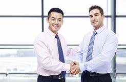 Homens de negócios que agitam as mãos no aeroporto Imagens de Stock Royalty Free