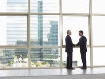 Homens de negócios que agitam as mãos no escritório Foto de Stock Royalty Free