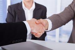 Homens de negócios que agitam as mãos no escritório Imagens de Stock Royalty Free