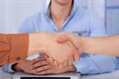 Homens de negócios que agitam as mãos no escritório Foto de Stock