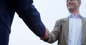 Homens de negócios que agitam as mãos um com o otro 4k filme