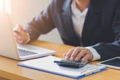 Homens de negócios que analisam dados financeiros do stats no portátil do PC, apontando na tela com o gráfico e as cartas de aume fotografia de stock