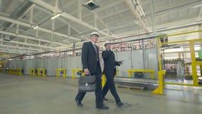 Homens de negócios que andam através da fábrica industrial vídeos de arquivo