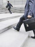 Homens de negócios que apressam-se acima das etapas fora Fotografia de Stock Royalty Free