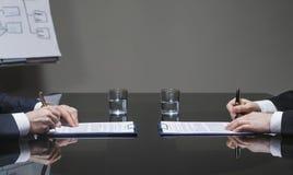 Homens de negócios que assinam contratos imagem de stock