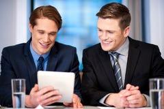 Homens de negócios que consultam no dispositivo da tabuleta Fotos de Stock