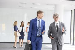 Homens de negócios que discutem ao andar contra colegas no escritório fotografia de stock
