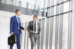 Homens de negócios que discutem ao andar no escritório fotografia de stock