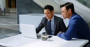 Homens de negócios que discutem sobre o portátil na tabela 4k video estoque