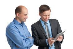 Homens de negócios que encontram e que olham o computador da tabuleta imagem de stock