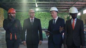 Homens de negócios que encontram-se no armazém video estoque