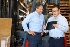Homens de negócios que encontram-se pelo caminhão de empilhadeira no armazém Fotos de Stock Royalty Free