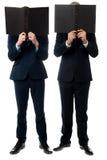 Homens de negócios que escondem suas caras com dobrador imagem de stock royalty free
