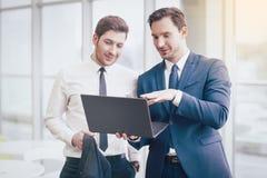Homens de negócios que fazem o projeto com um portátil imagem de stock royalty free