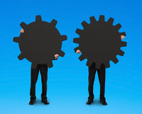 Homens de negócios que guardam duas engrenagens para conectar Foto de Stock