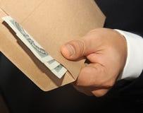 Homens de negócios que guardam o dinheiro 100 dólares em um envelo Fotos de Stock Royalty Free