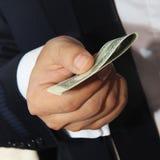 Homens de negócios que guardam o dinheiro 100 dólares que propõem o a você Imagens de Stock Royalty Free