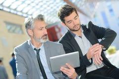 Homens de negócios que guardam a tabuleta e que olham o relógio foto de stock royalty free