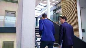Homens de negócios que interagem um com o otro ao andar em escadas filme