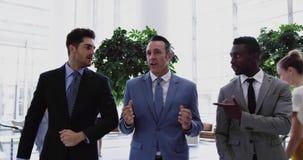 Homens de negócios que interagem um com o otro na entrada no escritório 4k vídeos de arquivo