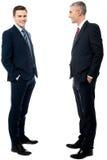 Homens de negócios que levantam com mãos em uns bolsos imagens de stock royalty free